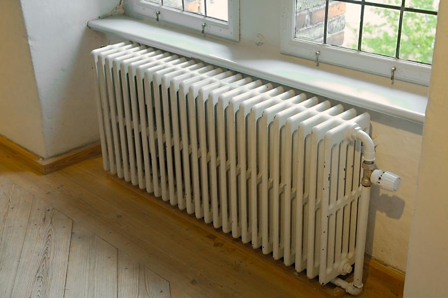 Photo of a steam heat radiator next to a window