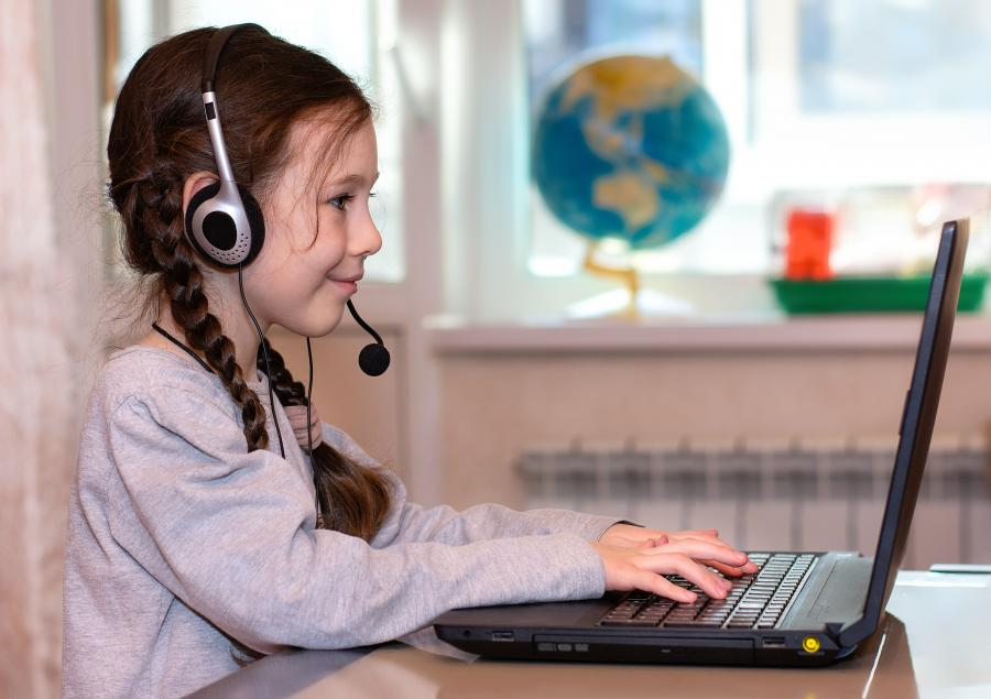 A girl with a headset on types on a laptop