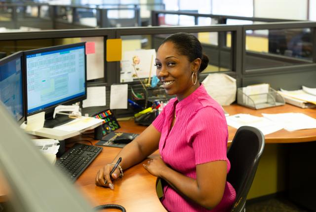 Customer Service Representative Natasha Butler smiles while sitting at her desk