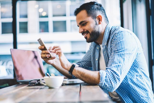 Stock image of cheerful male browsing the internet on his phone at a coffee shop
