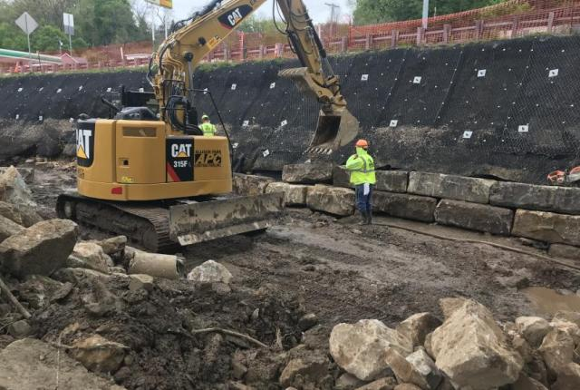 Crews place boulders as part of Saw Mill Run Stream Restoration Project.